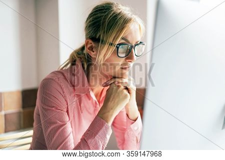 Business Woman In Glasses Looks At The Computer Monitor. Home Office. Remote Work. Professional Occu