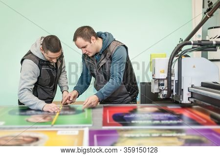 Worker Printmaker Measures And Checks Dimension With Ruler And Meter