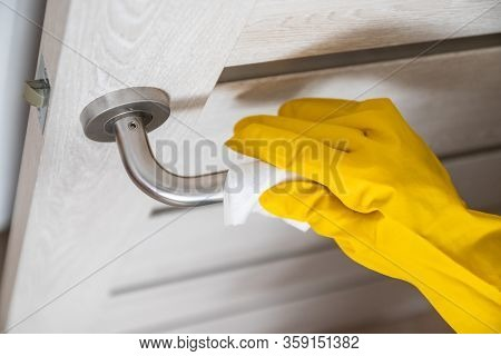 Coronavirus, Covid 19 Protection. Woman Disinfects And Cleans Door Handle With Antibacterial Wet Wip