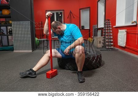 Potbellied Man Is Sitting On A Tire Exhausted After Performing Sledgehammer And Tire Training In The