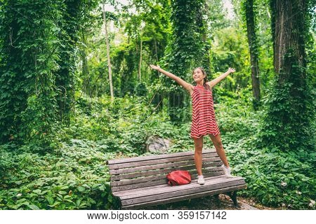 Happy Asian woman enjoying freedom in summer nature trees standing on park bench with arms outstretched in joy.