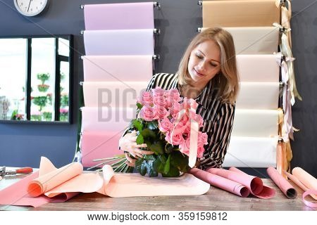 Florist Woman Makes A Bouquet Of Roses. Woman Florist In The Workplace. Pink Roses Beautiful Bouquet