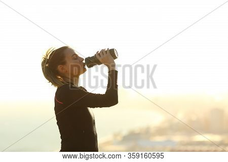 Side View Portrait Of A Runner Woman Drinking Water From Bottle Hydrating After Exercise In A City O