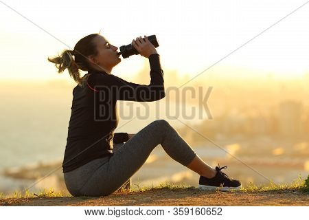 Runner Resting Hydrating Drinking Water At Sunset