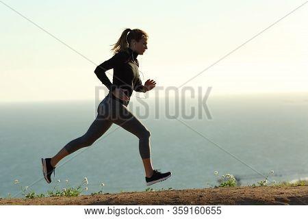 Runner Silhouette Running On The Beach