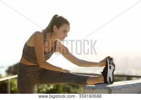 Runner Stretching Leg After Sport Outdoors