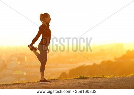 Full Body Profile Of A Runner Woman Stretching Leg Alone In City Outskirts At Sunset