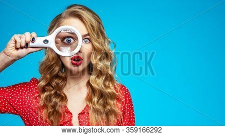 Surprised blonde holds a magnifying glass in front eye. Wonder young woman holds a magnifying glass in front of her eye. Funny girl with a bright smile and loupe. Eyesight care. Funny face of a girl