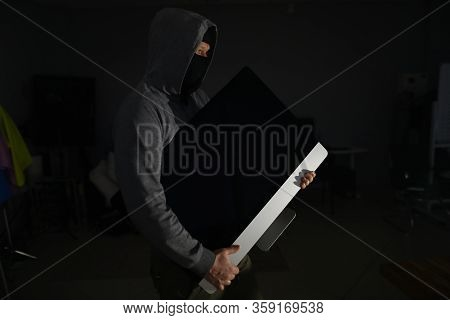 Portrait Of Man Wearing Grey Hoodie And Black Mask. Male Thief Standing In Dark Room And Holding Exp