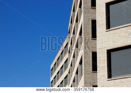 Exterior View Of A Modern Multi Storey Office Building Wiith Large Windows Framed In Brickwork Facad