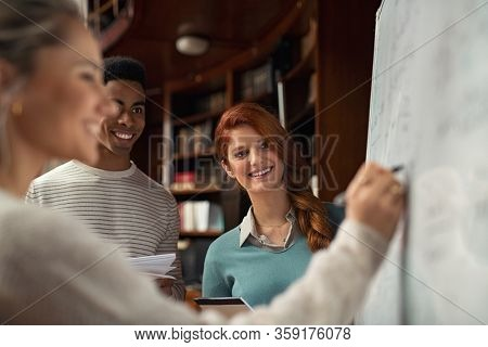 Happy multiethnic group students watching girl while she is writing on white board in library. Cheerful guy and smiling girl standing and taking notes while a friend solves equation during lesson.
