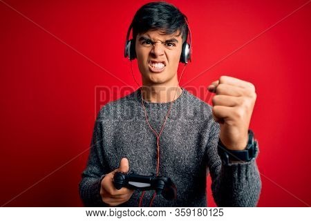 Young handsome gamer man playing video game using joystick and headphones annoyed and frustrated shouting with anger, crazy and yelling with raised hand, anger concept