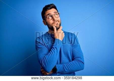 Young handsome man with beard wearing casual sweater and glasses over blue background Thinking worried about a question, concerned and nervous with hand on chin