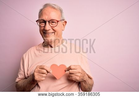 Senior grey haired man holding heart shape paper over pink background with a happy face standing and smiling with a confident smile showing teeth