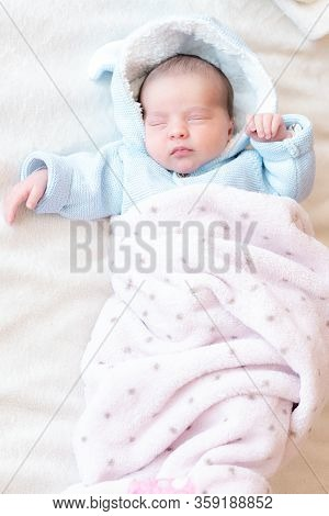 Newborn Baby Close-up, Place For Text. Newborn Sleeping On His Back In A Blue Blouse On A White Back