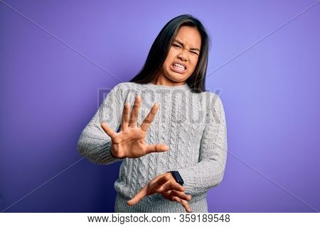 Young beautiful asian girl wearing casual sweater standing over isolated purple background disgusted expression, displeased and fearful doing disgust face because aversion reaction. With hands raised