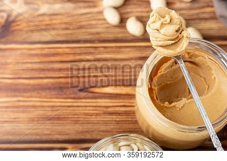 Creamy Peanut Paste In Open Glass Jar, Peanut Butter In Spoon. Peanuts In The Peel Scattered On The