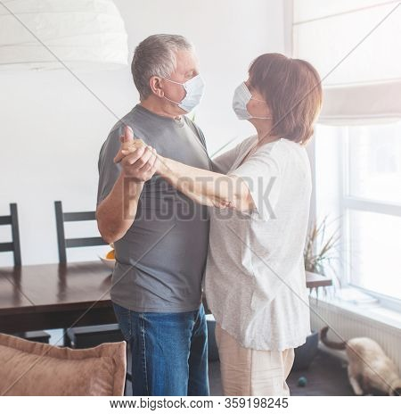 Coronavirus CoVid-19 Couple old aged senior people at home with seasona cold illness disease dancing. Elderly couple in medical masks during the pandemic