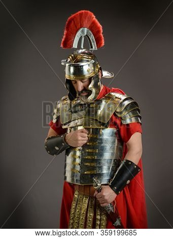 Roman soldier in actitud of submission isolated on a gray background
