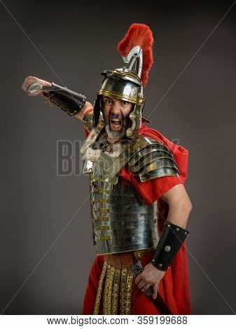 Roman soldier holding his sword ready to atack isoladed on a dark background