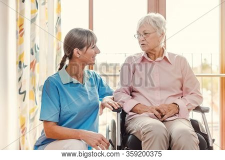 Caregiver with senior woman in pension home by the window