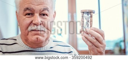 Senior man holding hourglass in retirement home, symbol for limited life span
