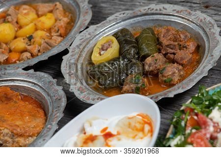 Eid Mubarak Traditional Ramadan Iftar dinner. Assorted tasty food in authentic rustic dishes on wooden blue background.  Turkish Bosnian food meat kebab, pita, Sarma, klepe, sogan dolma,