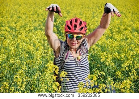 Woman With Cycling Helmet Posing Like A Zombie In A Rapeseed Field.