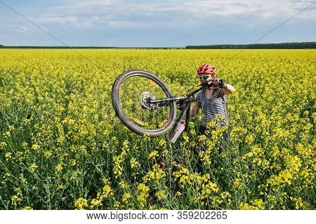 Female Cyclist Moves Through A Rapeseed Field On Foot, Lifting Her Mountain Bike On The Rear Wheel.