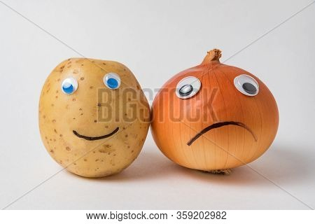 Positive Potato And A Sad Napiform Onion With Googly Eyes On A White Background. Pessimist And Optim
