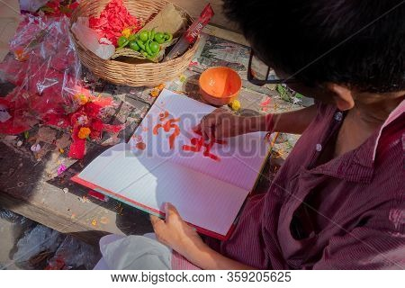 Kalighat, Kolkata, West Bengal, India - April 15th 2019 : Hindu Priest Drawing Auspicious Religious