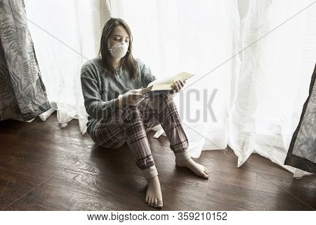 A Concept Photo Of A Teen Girl With A Mask, Gloves,  And A Book Showing The Boredom Of Staying At Ho