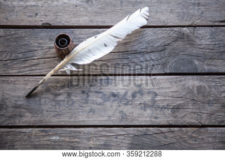 Feather for writing and inkwell .Quill for writing. The feather lies on an old wooden table with inkwell . Beautiful background for napkins, wallpapers, books, notebooks, paper.
