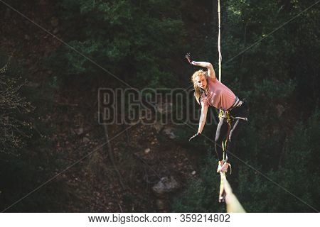 A Woman Is Walking Along A Stretched Sling Over A Forest, Highliner Balances Over The Abyss, Highlin