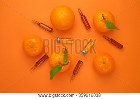 Vitamin C Concept. Tangerines Citrus Fruits, Vitamin C In Glass Ampoules On A Bright Orange Backgrou