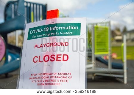 A Closed Playground Sign For Covid-19 Infront Of A Little Kids Playground.