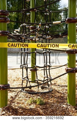 Climbing Rope Structure At A Playground Is Caution Taped Off Due To Covid-19 Isolation Measures.