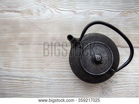 Black Metall Tea Pot On A White Wooden Background