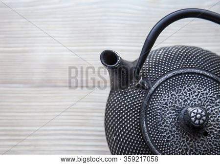 Part Of Black Metall Tea Pot On A White Wooden Background