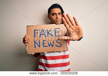 Young african american man with dreadlocks holding banner with fake news message protest with open hand doing stop sign with serious and confident expression, defense gesture