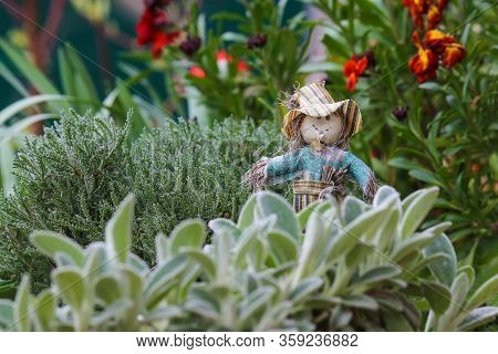 Toy Smiling Scarecrow With A Dandelion Flower In Hand On A Blurred Background Of Green Grass In A Fl