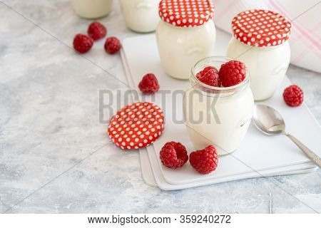Natural Homemade Yogurt In Reusable Glass Jars Decorated With Fresh Raspberries. Delicious Natural Y