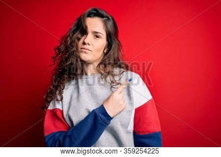 Young beautiful woman with curly hair wearing casual sweatshirt over isolated red background Pointing with hand finger to the side showing advertisement, serious and calm face