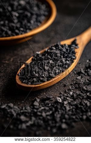 Close Up Of Black Salt Crystals In Wooden Spoon On Black Background