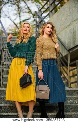 Sweater Skirt Trend. Matching Outfits. Women Sisters Outdoors Stairs Background. Matching Colors. Pe