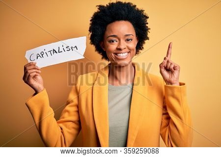 African American afro businesswoman with curly hair holding paper with capitalism message surprised with an idea or question pointing finger with happy face, number one