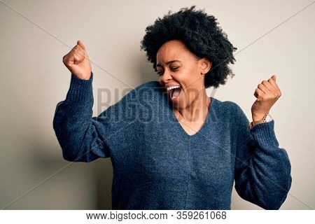 Young beautiful African American afro woman with curly hair wearing casual sweater Dancing happy and cheerful, smiling moving casual and confident listening to music