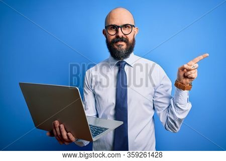 Handsome bald business man with beard working using laptop over blue background very happy pointing with hand and finger to the side