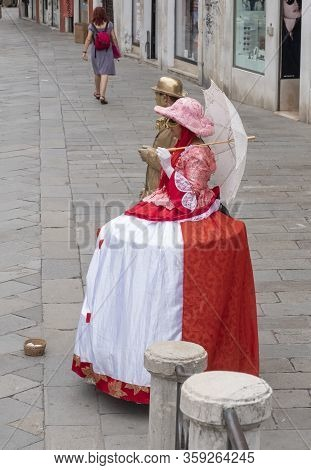 Venice, Italy - June 30, 2017: Two People In Woman Red Venetian Clothes, Man In Goldcolored Clothes