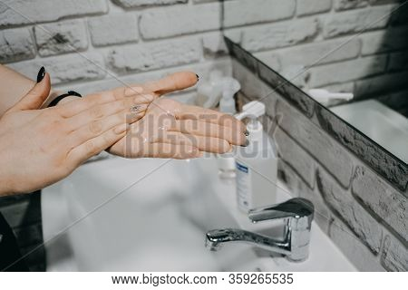 Gel Hand Sanitisers Protect Against The New Coronavirus. Woman Using Bottle Of Antibacterial Sanitis